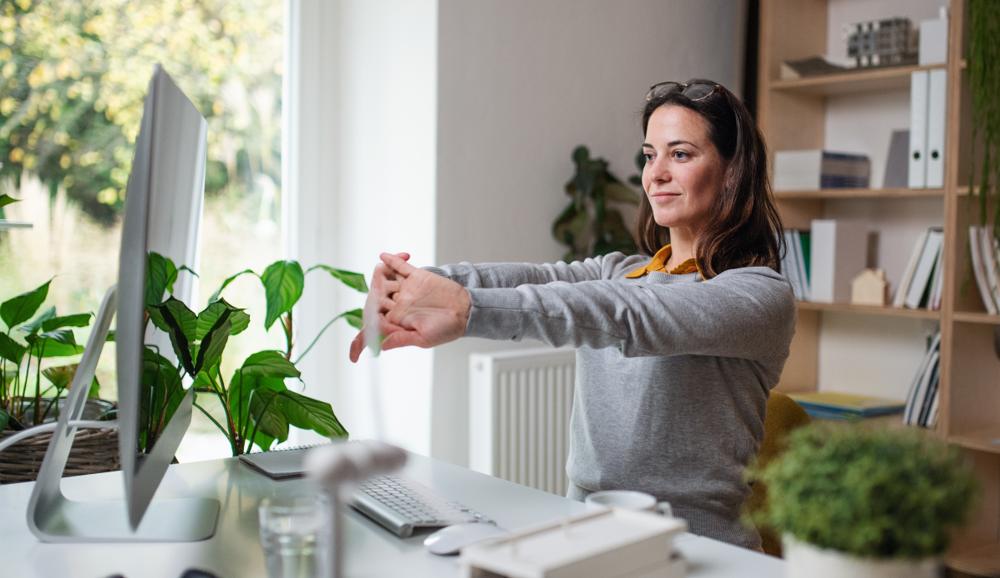 Frau macht Dehnübung am Schreibtisch - Arbeitsschutz Homeoffice